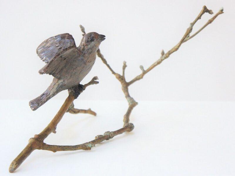 bronzen beeld mus op takje